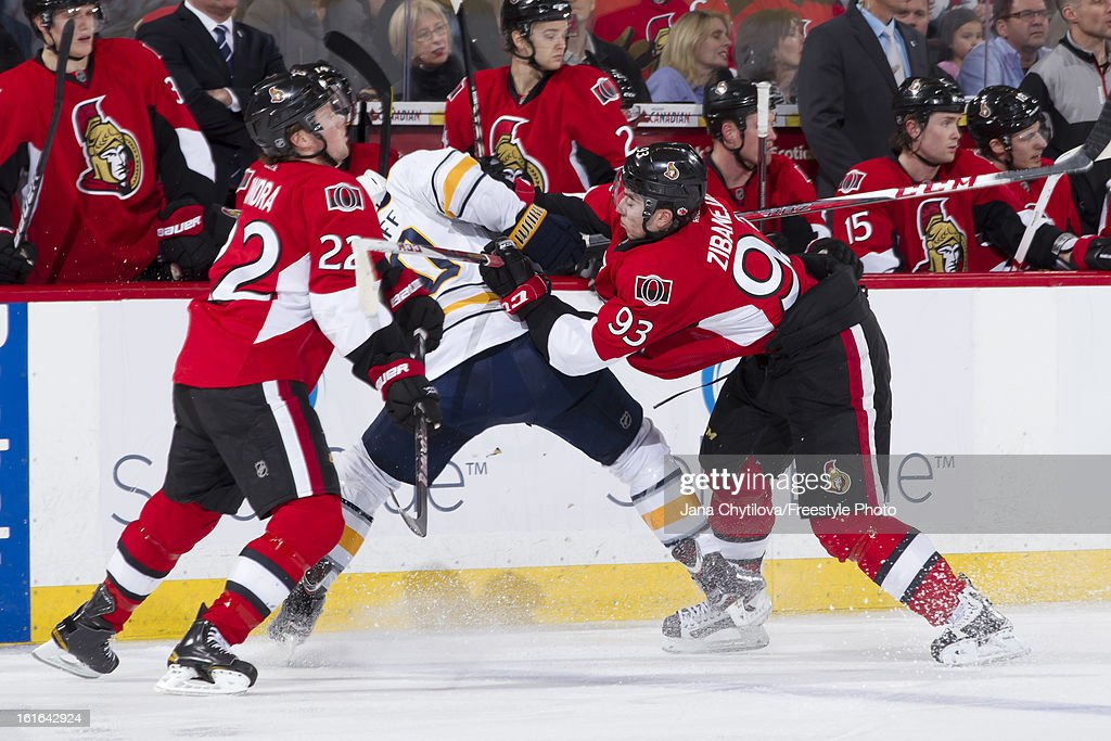 Mika Zibanejad #93 of the Ottawa Senators checks Christian Ehrhoff #10 of the Buffalo Sabres as Erik Condra #22 of the Ottawa Senators reacts to the check, during an NHL game at Scotiabank Place on February 12, 2013 in Ottawa, Ontario, Canada.