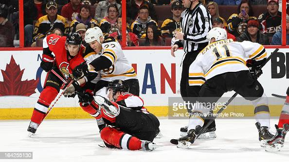 Mika Zibanejad of the Ottawa Senators falls to the ice as he wins the faceoff against Gregory Campbell of the Boston Bruins and Mike Lundin of the...