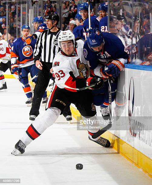 Mika Zibanejad of the Ottawa Senators hits Frans Nielsen of the New York Islanders into the boards during the second period at the Nassau Veterans...