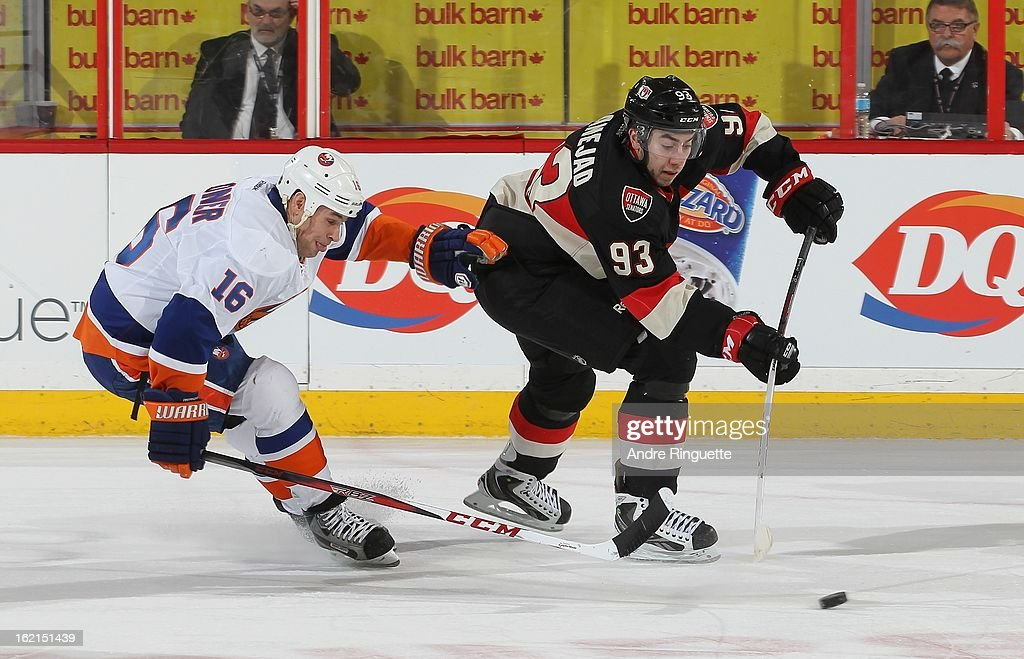 Mika Zibanejad of the Ottawa Senators passes the puck against Marty Reasoner of the New York Islanders on February 19 2013 at Scotiabank Place in...