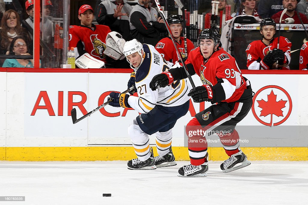 Mika Zibanejad #93 of the Ottawa Senators skates for the loose puck against Adam Pardy #27 of the Buffalo Sabres during an NHL game at Scotiabank Place on February 5, 2013 in Ottawa, Ontario, Canada.