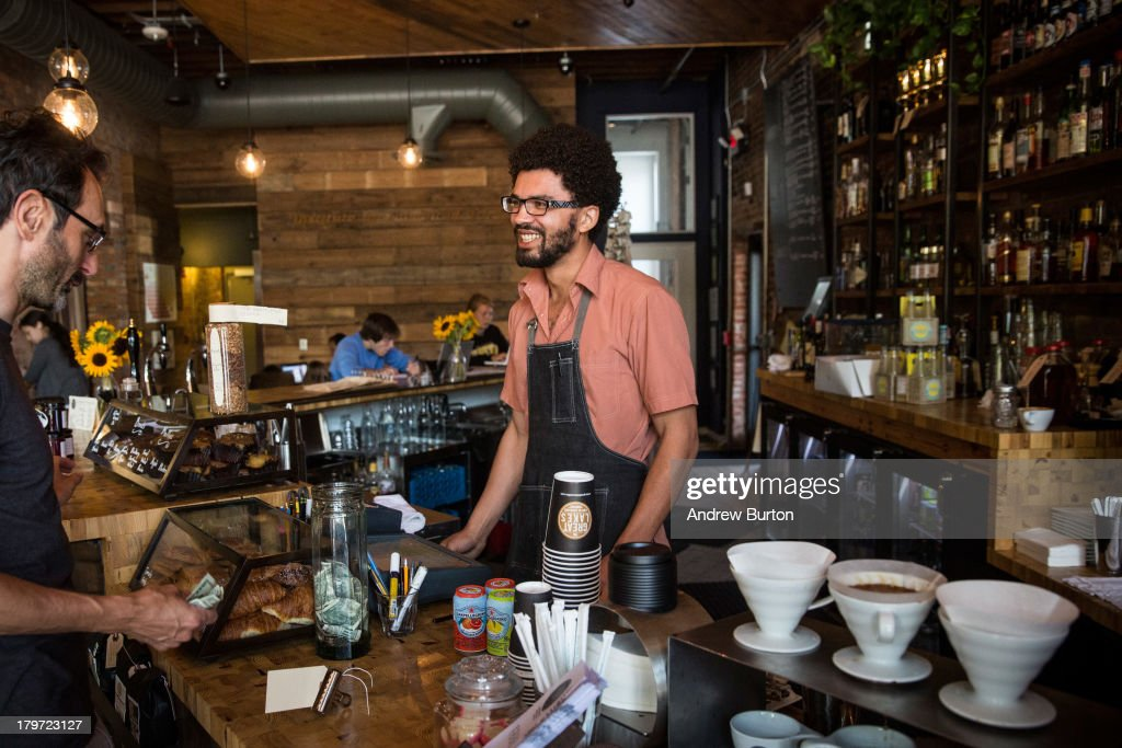 Mikael Addae (C), a barista at Great Lakes Coffee Roasting Company, helps a customer on September 6, 2013 in Detroit, Michigan. Great Lakes Coffee Roasting opened 14 months ago, and has since become a popular spot for a growing community of creative-types to meet, work on laptops and sip on a coffee or beer. Despite over 78,000 abandoned homes across 140 square miles, 16% unemployment and the city declaring bankrupty in July, Detroit has attracted a booming creative class in the past five years.