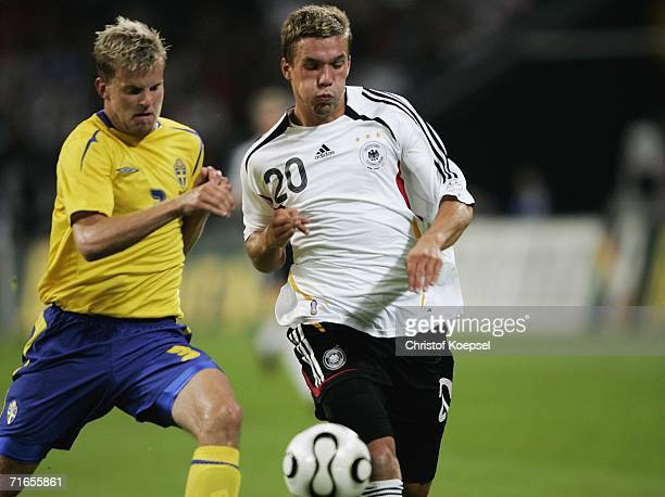 Mikael Antonsson of Sweden tackles Lukas Podolski of Germany during the friendly match between Germany and Sweden at the Arena Auf Schalke on August...