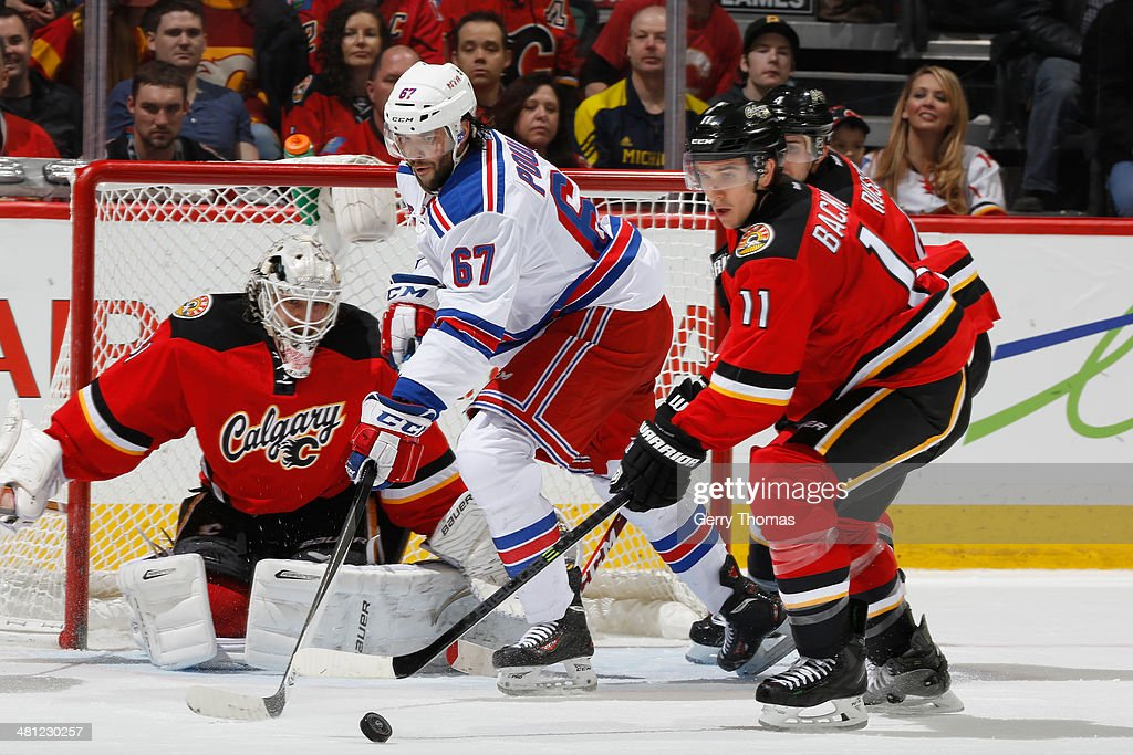 Mikael Backlund #11 and Karri Ramo #31 of the Calgary Flames defend the net against Benoit Pouliot #67 of the New York Rangers at Scotiabank Saddledome on March 28, 2014 in Calgary, Alberta, Canada.