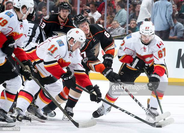 Mikael Backlund and Michael Frolik of the Calgary Flames battle for the puck with Rickard Rakell of the Anaheim Ducks during the first period of the...