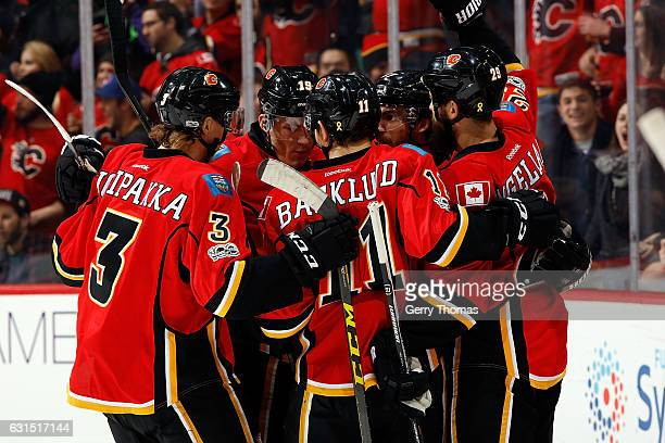 Mikael Backlund Jyrki Jokipakka and teammates of the Calgary Flames celebrate a goal against the San Jose Sharks during an NHL game on January 11...