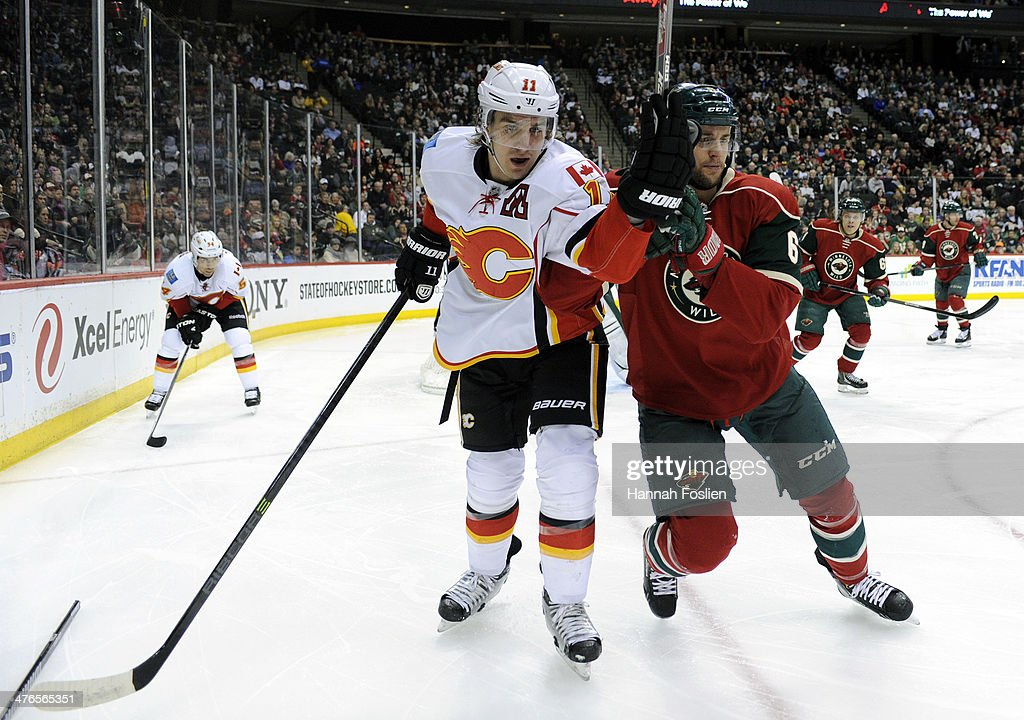 Mikael Backlund #11 of the Calgary Flames and Marco Scandella #6 of the Minnesota Wild skate after the puck during the first period of the game on March 3, 2014 at Xcel Energy Center in St Paul, Minnesota.