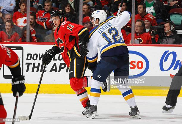 Mikael Backlund of the Calgary Flames battles for the puck against Jori Lehtera of the St Louis Blues at Scotiabank Saddledome on March 17 2015 in...