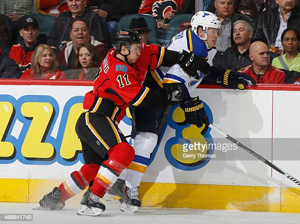 Mikael Backlund of the Calgary Flames battles on the boards against the St Louis Blues at Scotiabank Saddledome on March 17 2015 in Calgary Alberta...