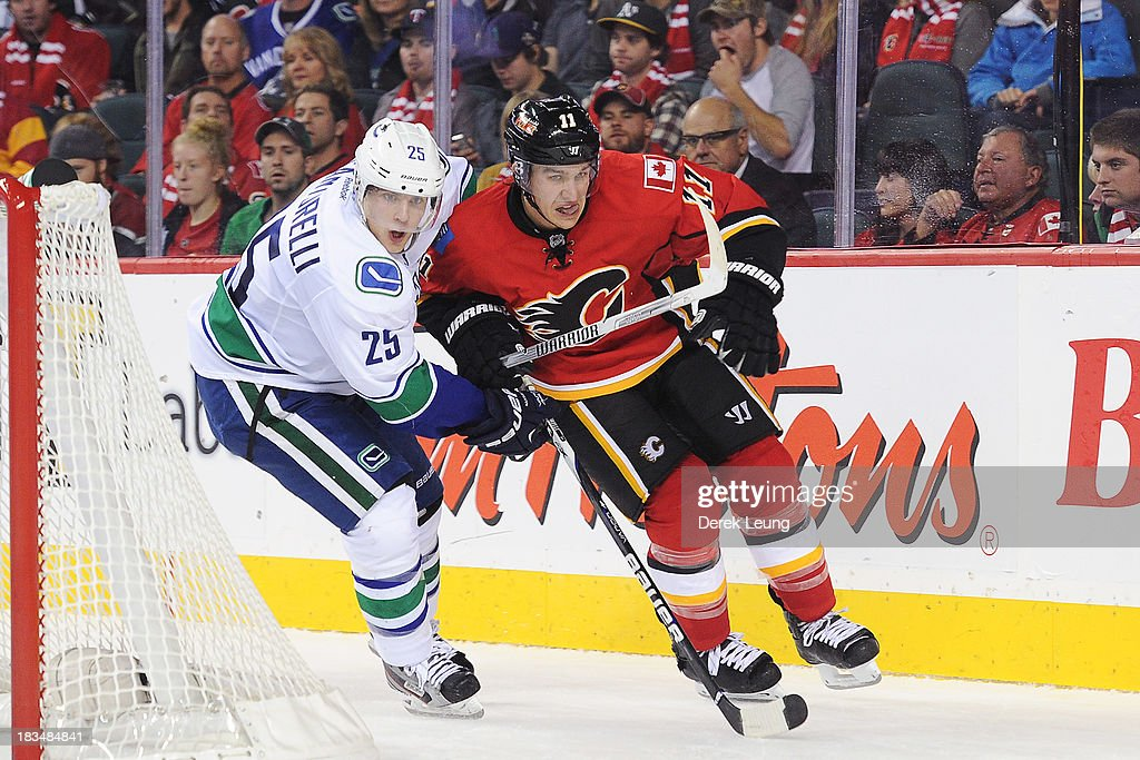 <a gi-track='captionPersonalityLinkClicked' href=/galleries/search?phrase=Mikael+Backlund&family=editorial&specificpeople=4324942 ng-click='$event.stopPropagation()'>Mikael Backlund</a> #11 of the Calgary Flames chases the puck against <a gi-track='captionPersonalityLinkClicked' href=/galleries/search?phrase=Mike+Santorelli&family=editorial&specificpeople=4517042 ng-click='$event.stopPropagation()'>Mike Santorelli</a> #25 of the Vancouver Canucks during the Flames' home opening NHL game at Scotiabank Saddledome on October 6, 2013 in Calgary, Alberta, Canada. The Vancouver Canucks won 5-4 in OT.