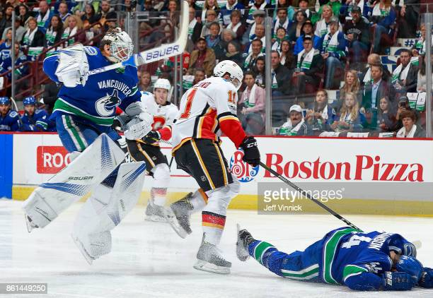 Mikael Backlund of the Calgary Flames collides with Erik Gudbranson of the Vancouver Canucks during their NHL game at Rogers Arena October 14 2017 in...
