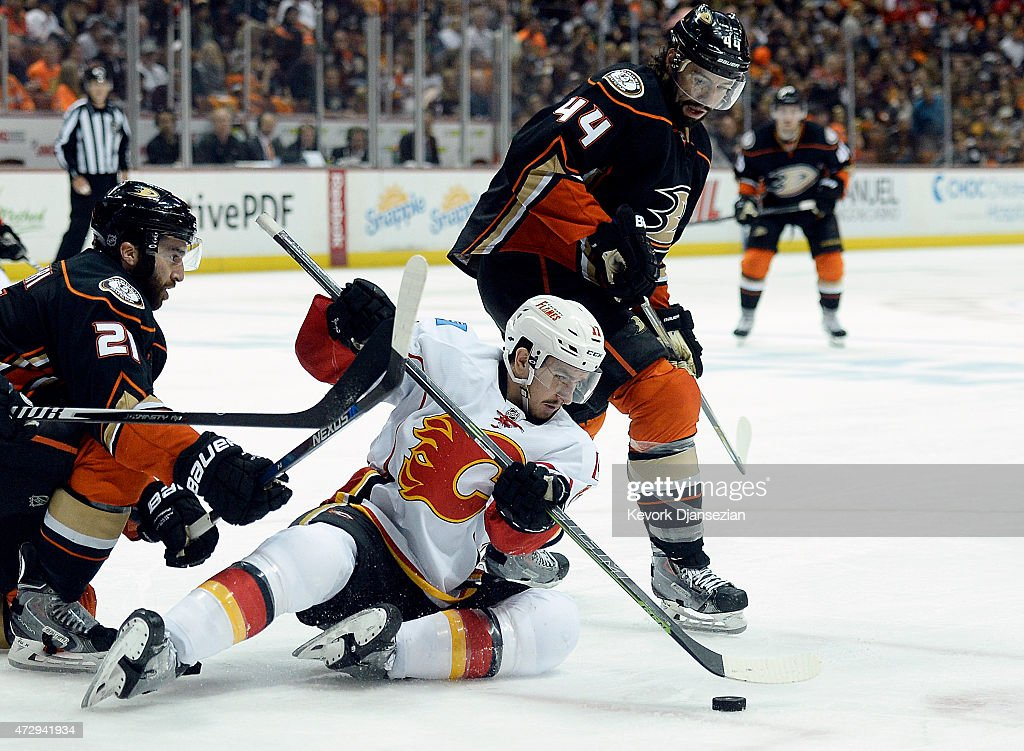Mikael Backlund #11 of the Calgary Flames controls the puck against Kyle Palmieri #21 and Nate Thompson #44 of the Anaheim Ducks in Game Five of the Western Conference Semifinals during the 2015 Stanley Cup Playoffs at Honda Center on May 10, 2015 in Anaheim, California.