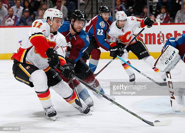 Mikael Backlund of the Calgary Flames earns an assist as he has his shot deflected by goalie Semyon Varlamov of the Colorado Avalanche as David Jones...
