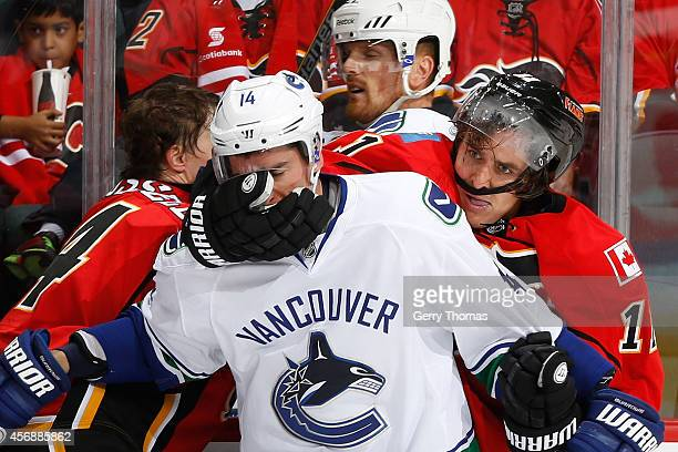 Mikael Backlund of the Calgary Flames gets into a physical altercation with Alexandre Burrows of the Vancouver Canucks in their NHL season opener at...