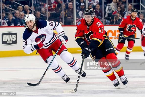 Mikael Backlund of the Calgary Flames plays the puck down the ice as Chris Thorburn of the Winnipeg Jets gives chase during first period action at...