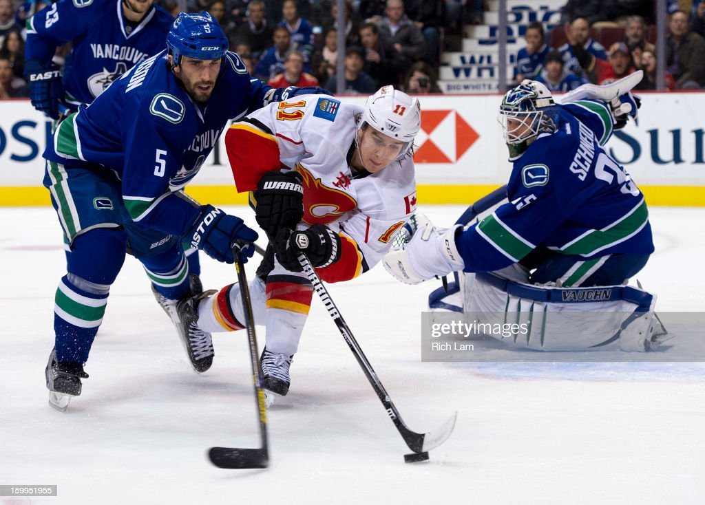 Mikael Backlund #11 of the Calgary Flames reaches for the loose puck while being checked by Jason Garrison #5 of the Vancouver Canucks after goalie Cory Schneider #35 of the Vancouver Canucks made the save during the first period of NHL action on January 23, 2013 at Rogers Arena in Vancouver, British Columbia, Canada.