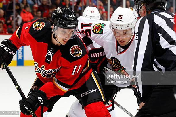 Mikael Backlund of the Calgary Flames skates against Artem Ansimov of the Chicago Blackhawks during an NHL game at Scotiabank Saddledome on March 26...