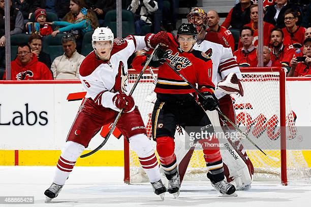 Mikael Backlund of the Calgary Flames skates against Connor Murphy of the Arizona Coyotes at Scotiabank Saddledome on April 7 2015 in Calgary Alberta...