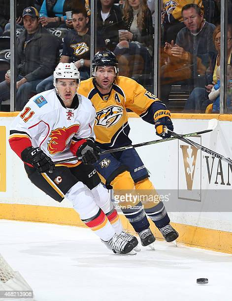 Mikael Backlund of the Calgary Flames skates against Mike Fisher of the Nashville Predators during an NHL game at Bridgestone Arena on March 29 2015...