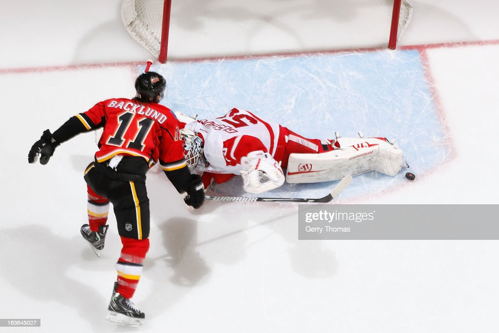 <a gi-track='captionPersonalityLinkClicked' href=/galleries/search?phrase=Mikael+Backlund&family=editorial&specificpeople=4324942 ng-click='$event.stopPropagation()'>Mikael Backlund</a> #11 of the Calgary Flames takes a shot against <a gi-track='captionPersonalityLinkClicked' href=/galleries/search?phrase=Jonas+Gustavsson&family=editorial&specificpeople=886789 ng-click='$event.stopPropagation()'>Jonas Gustavsson</a> #50 of the Detroit Red Wings on March 13, 2013 at the Scotiabank Saddledome in Calgary, Alberta, Canada.