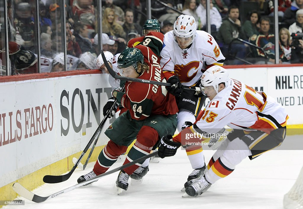 Mikael Granlund #64 of the Minnesota Wild along with David Jones #54 and Mike Cammalleri #13 of the Calgary Flames skate after the puck during the first period of the game on March 3, 2014 at Xcel Energy Center in St Paul, Minnesota.