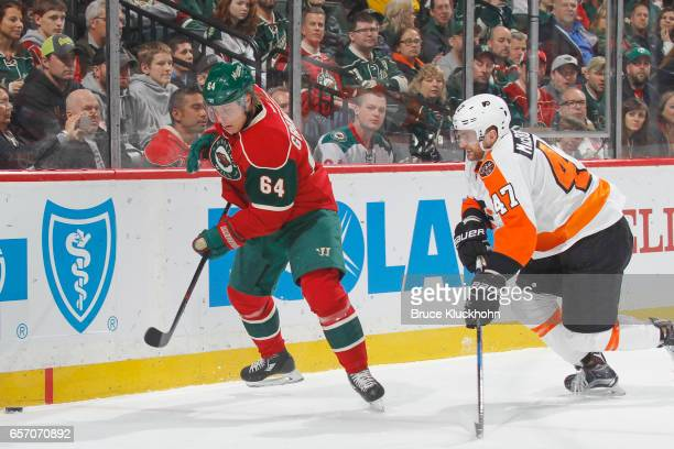 Mikael Granlund of the Minnesota Wild and Andrew MacDonald of the Philadelphia Flyers skate to the puck during the game on March 23 2017 at the Xcel...