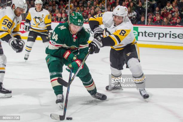 Mikael Granlund of the Minnesota Wild and Brian Dumoulin of the Pittsburgh Penguins battle for the puck during the game at the Xcel Energy Center on...