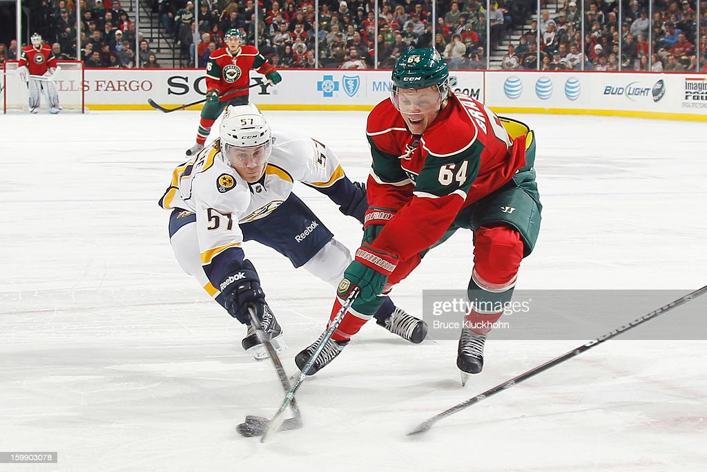 Mikael Granlund #64 of the Minnesota Wild and Gabriel Bourque #57 of the Nashville Predators battle for control of the puck during the game on January 22, 2013 at the Xcel Energy Center in Saint Paul, Minnesota.