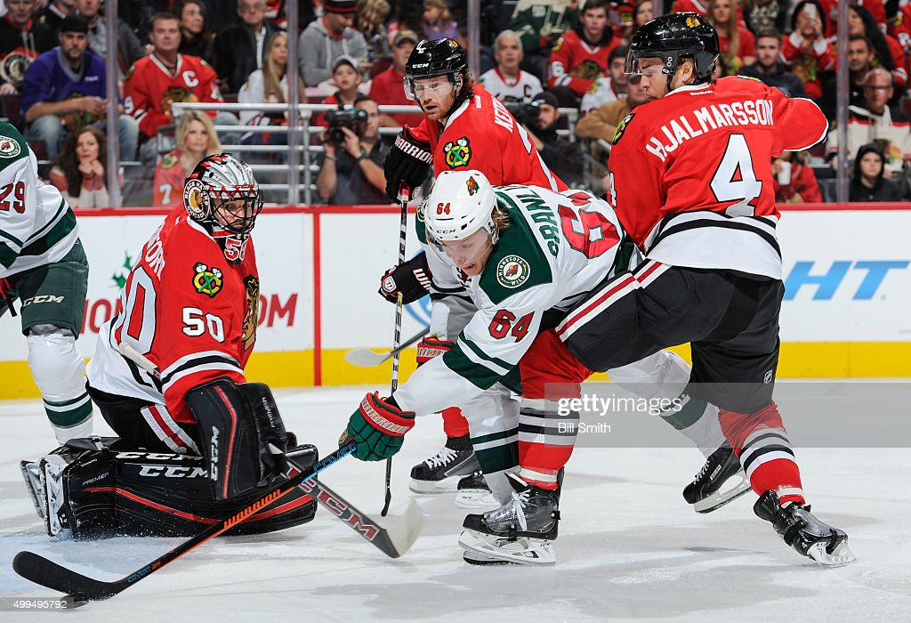 <a gi-track='captionPersonalityLinkClicked' href=/galleries/search?phrase=Mikael+Granlund&family=editorial&specificpeople=5649678 ng-click='$event.stopPropagation()'>Mikael Granlund</a> #64 of the Minnesota Wild assists on a goal against goalie <a gi-track='captionPersonalityLinkClicked' href=/galleries/search?phrase=Corey+Crawford&family=editorial&specificpeople=818935 ng-click='$event.stopPropagation()'>Corey Crawford</a> #50 of the Chicago Blackhawks, as <a gi-track='captionPersonalityLinkClicked' href=/galleries/search?phrase=Niklas+Hjalmarsson&family=editorial&specificpeople=2006442 ng-click='$event.stopPropagation()'>Niklas Hjalmarsson</a> #4 defends, in the first period of the NHL game at the United Center on December 1, 2015 in Chicago, Illinois.