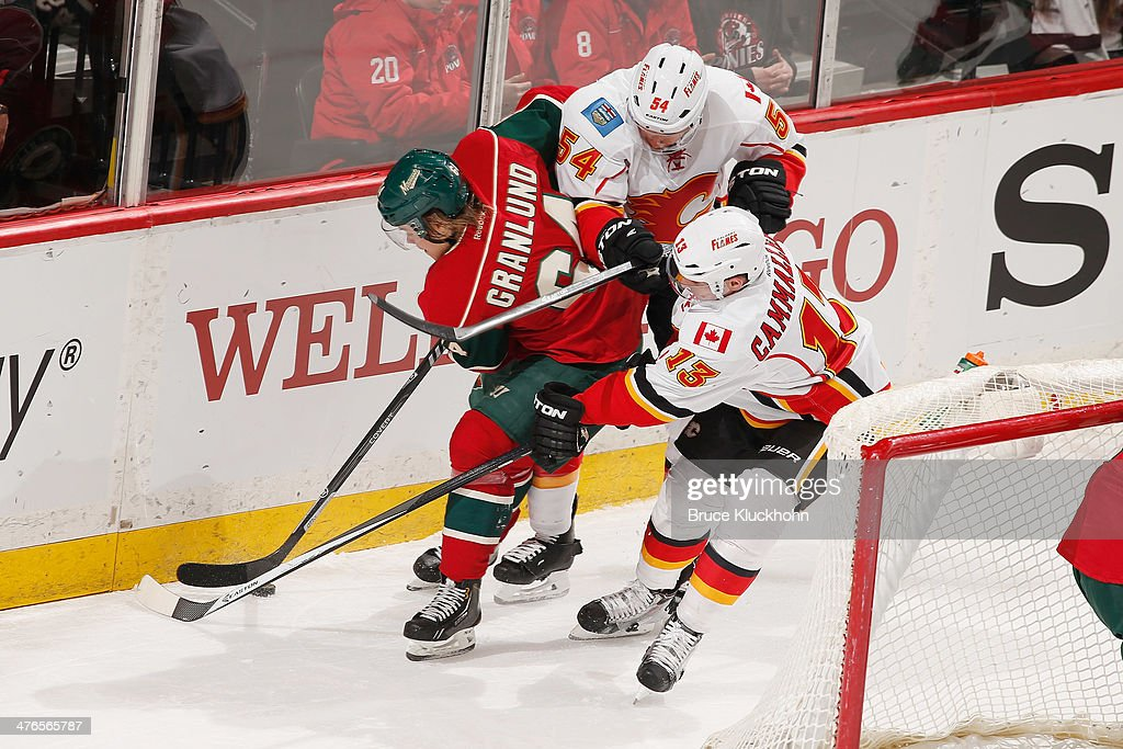 Mikael Granlund #64 of the Minnesota Wild battles for the puck with (R-L) Mike Cammalleri #13 and David Jones #54 of the Calgary Flames during the game on March 3, 2014 at the Xcel Energy Center in St. Paul, Minnesota.