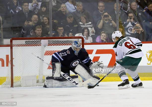 Mikael Granlund of the Minnesota Wild carries the puck in on goaltender Connor Hellebuyck of the Winnipeg Jets during a third period penalty shot at...