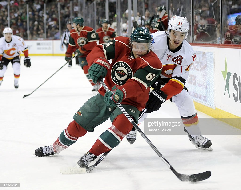 Mikael Granlund #64 of the Minnesota Wild passes the puck away from Mikael Backlund #11 of the Calgary Flames during the first period of the game on March 3, 2014 at Xcel Energy Center in St Paul, Minnesota.
