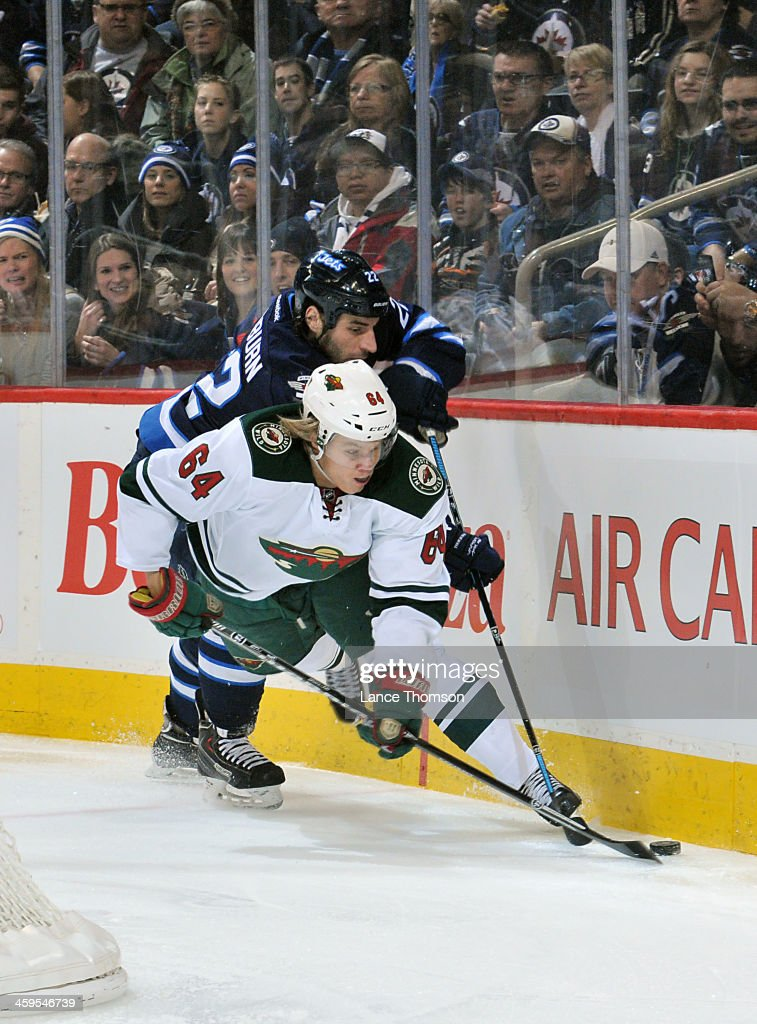 <a gi-track='captionPersonalityLinkClicked' href=/galleries/search?phrase=Mikael+Granlund&family=editorial&specificpeople=5649678 ng-click='$event.stopPropagation()'>Mikael Granlund</a> #64 of the Minnesota Wild plays the puck along the boards as <a gi-track='captionPersonalityLinkClicked' href=/galleries/search?phrase=Chris+Thorburn&family=editorial&specificpeople=2222066 ng-click='$event.stopPropagation()'>Chris Thorburn</a> #22 of the Winnipeg Jets chases from behind during first period action at the MTS Centre on December 27, 2013 in Winnipeg, Manitoba, Canada.
