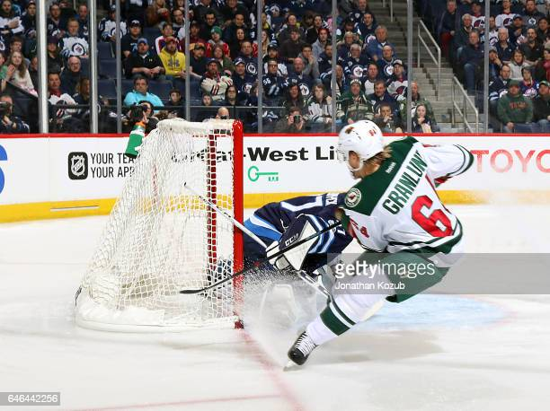 Mikael Granlund of the Minnesota Wild shoots the puck over a sprawling Connor Hellebuyck of the Winnipeg Jets for a first period goal at the MTS...