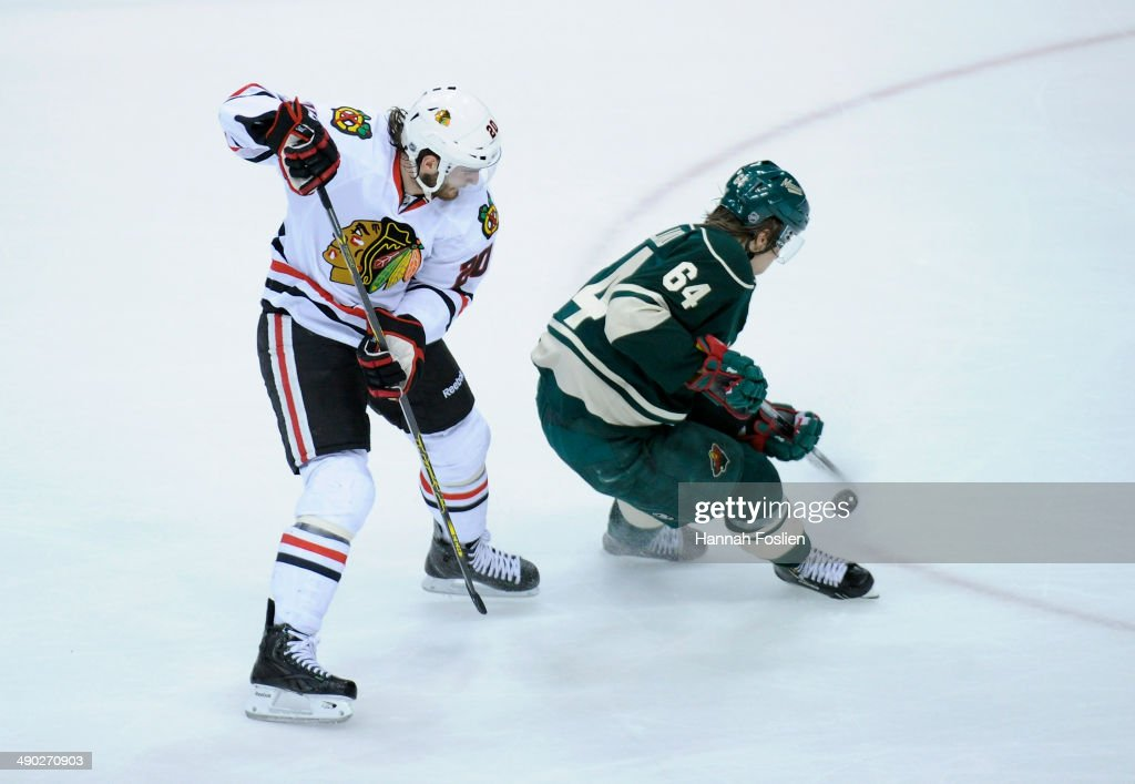 Mikael Granlund #64 of the Minnesota Wild takes the puck away from Brandon Saad #20 of the Chicago Blackhawks during the first period in Game Six of the Second Round of the 2014 NHL Stanley Cup Playoffs on May 13, 2014 at Xcel Energy Center in St Paul, Minnesota. The Blackhawks defeated the Wild 2-1 in overtime.