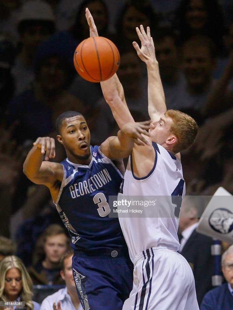 Mikael Hopkins #3 of the Georgetown Hoyas passes the ball as Erik Fromm #4 of the Butler Bulldogs defends at Hinkle Fieldhouse on January 11, 2014 in Indianapolis, Indiana.