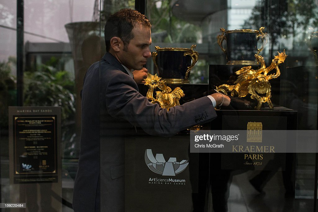 Mikael Kraemer dusts around a pair of dragon chased and gild bronze fire dogs from circa 1720 on display January 9, 2013 at Marina Bay Sands in Singapore. To commemorate the Year of The Dragon,the exhibition 'The Final 100 Days of the Year of the Dragon' showcases a selection of rare 18th century French 'Chinoiserie' furniture and ornaments from the Kraemer gallery collection in Paris. The Kraemer Gallery boasts the worlds largest privately-owned collection of French 18th century furniture and ornaments considered museum quality. The exhibition is on display until Chinese New Year on 10 February 2013.
