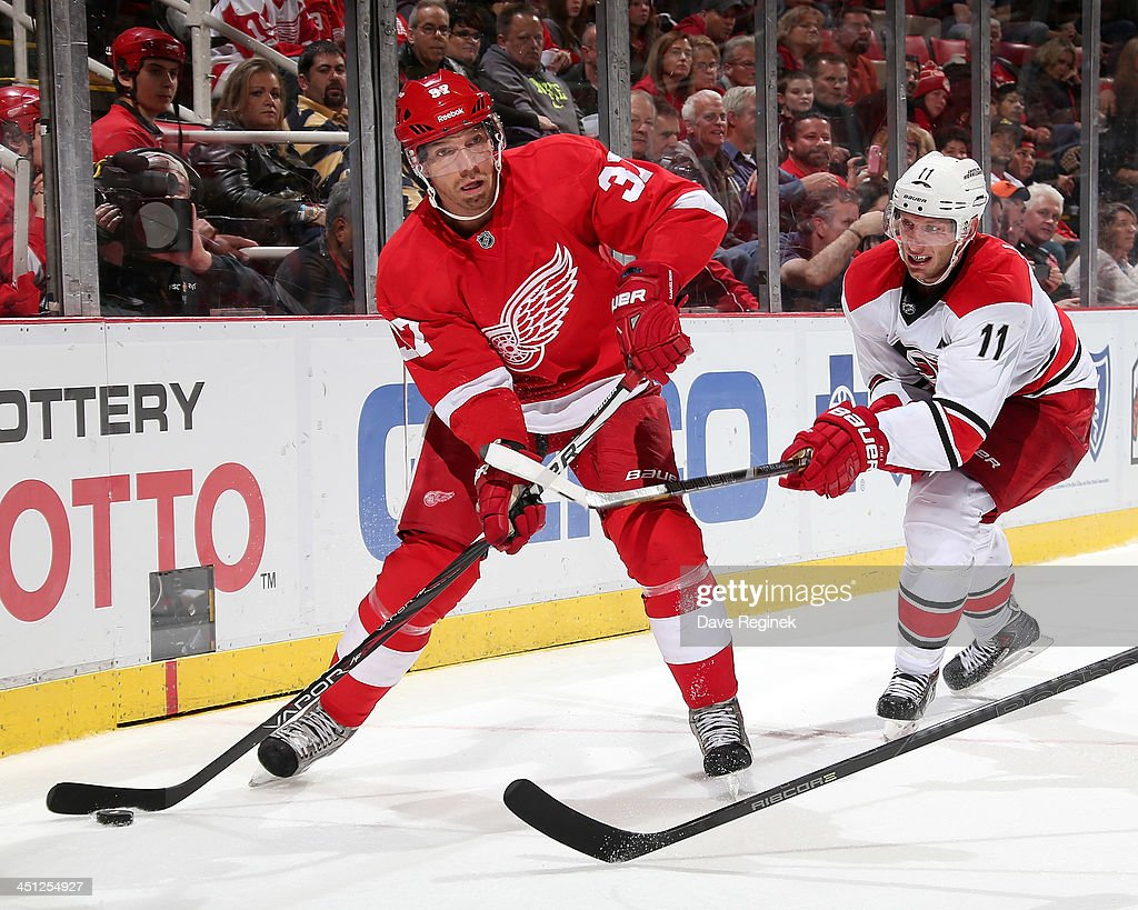 <a gi-track='captionPersonalityLinkClicked' href=/galleries/search?phrase=Mikael+Samuelsson&family=editorial&specificpeople=203085 ng-click='$event.stopPropagation()'>Mikael Samuelsson</a> #37 of the Detroit Red Wings passes the puck as <a gi-track='captionPersonalityLinkClicked' href=/galleries/search?phrase=Jordan+Staal&family=editorial&specificpeople=533044 ng-click='$event.stopPropagation()'>Jordan Staal</a> #11 of the Carolina Hurricanes slashes him during an NHL game at Joe Louis Arena on November 21, 2013 in Detroit, Michigan. Detroit defeated Carolina 4-3