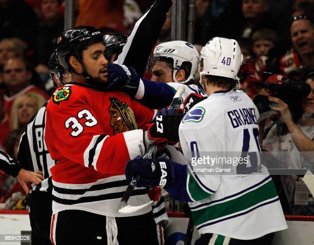 Mikael Samuelsson of the Vancouver Canucks reaches in to smack Dustin Byfuglien of the Chicago Blackhawks in front of Michael Grabner in Game Five of...