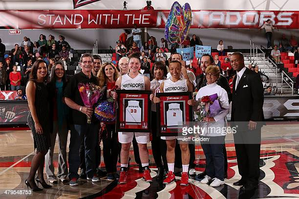 Mikayla Thielges and Haley White of the Cal State Northridge Matadors smile as they are honored at center court on senior night with their family and...