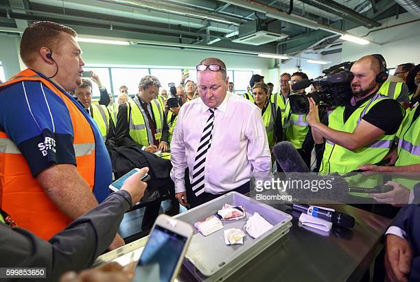 Mike Ashley billionaire and founder of Sports Direct International Plc looks at his wallet and a wad of 50 pound banknotes in a tray as he...