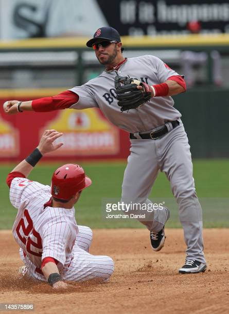 Mike Aviles of the Boston Red Sox turns a double play as Brent Morel of the Chicago White Sox slides into second at US Cellular Field on April 29...