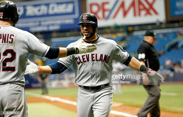 Mike Aviles of the Cleveland Indians celebrates with teammate Jason Kipnis following his home run during the 10th inning of a game against the Tampa...