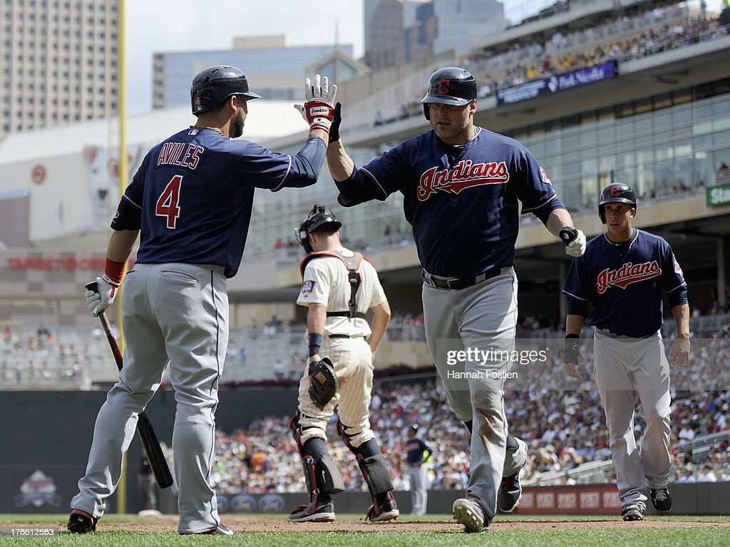 <a gi-track='captionPersonalityLinkClicked' href=/galleries/search?phrase=Mike+Aviles&family=editorial&specificpeople=4944765 ng-click='$event.stopPropagation()'>Mike Aviles</a> #4 of the Cleveland Indians congratulates teammate <a gi-track='captionPersonalityLinkClicked' href=/galleries/search?phrase=Jason+Giambi&family=editorial&specificpeople=194953 ng-click='$event.stopPropagation()'>Jason Giambi</a> #25 on a three run home run as <a gi-track='captionPersonalityLinkClicked' href=/galleries/search?phrase=Joe+Mauer&family=editorial&specificpeople=214614 ng-click='$event.stopPropagation()'>Joe Mauer</a> #7 of the Minnesota Twins looks on during the seventh inning of the game on August 14, 2013 at Target Field in Minneapolis, Minnesota.
