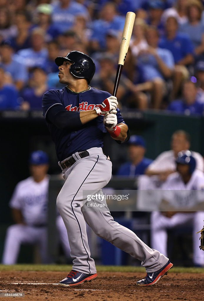 Mike Aviles #4 of the Cleveland Indians hits a sacrifice fly in the fourth inning against the Kansas City Royals at Kauffman Stadium on August 31, 2014 in Kansas City, Missouri.