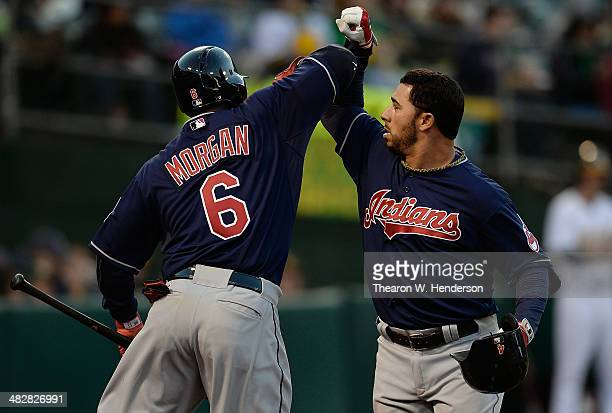 Mike Aviles of the Cleveland Indians is congratulated by Nyjer Morgan after Aviles hit a tworun homer against the Oakland Athletics in the top of the...