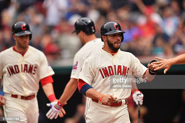 Mike Aviles of the Cleveland Indians right and Yan Gomes of the Cleveland Indians left celebrate after scoring in the sixth inning off an errant...