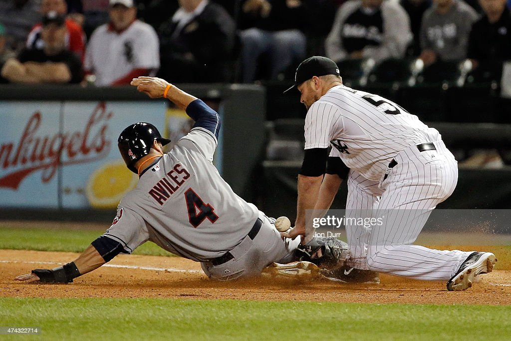 <a gi-track='captionPersonalityLinkClicked' href=/galleries/search?phrase=Mike+Aviles&family=editorial&specificpeople=4944765 ng-click='$event.stopPropagation()'>Mike Aviles</a> #4 of the Cleveland Indians slides safely into first base as <a gi-track='captionPersonalityLinkClicked' href=/galleries/search?phrase=John+Danks&family=editorial&specificpeople=835613 ng-click='$event.stopPropagation()'>John Danks</a> #50 of the Chicago White Sox attempts the tag after being caught in a run down during the sixth inning on May 21, 2015 at U.S. Cellular Field in Chicago, Illinois. The Cleveland Indians won 5-2.