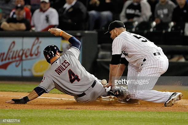 Mike Aviles of the Cleveland Indians slides safely into first base as John Danks of the Chicago White Sox attempts the tag after being caught in a...