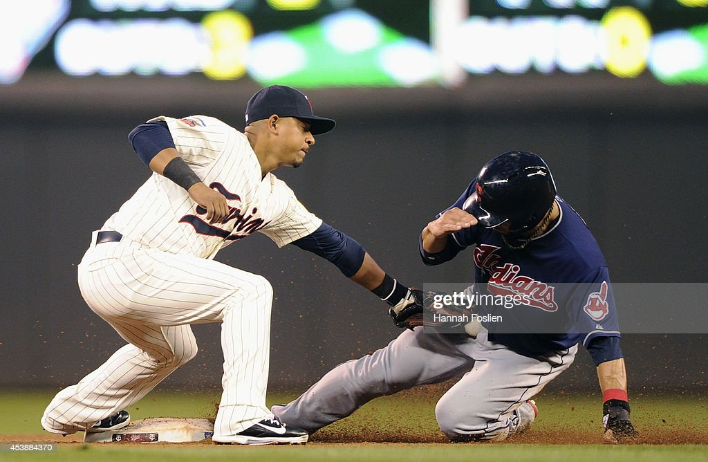 Mike Aviles #4 of the Cleveland Indians steals second base under the tag of Eduardo Escobar #5 of the Minnesota Twins during the fourth inning of the game on August 20, 2014 at Target Field in Minneapolis, Minnesota. The play was officially reviewed after Aviles was initially called out. The Indians defeated the Twins 5-0.